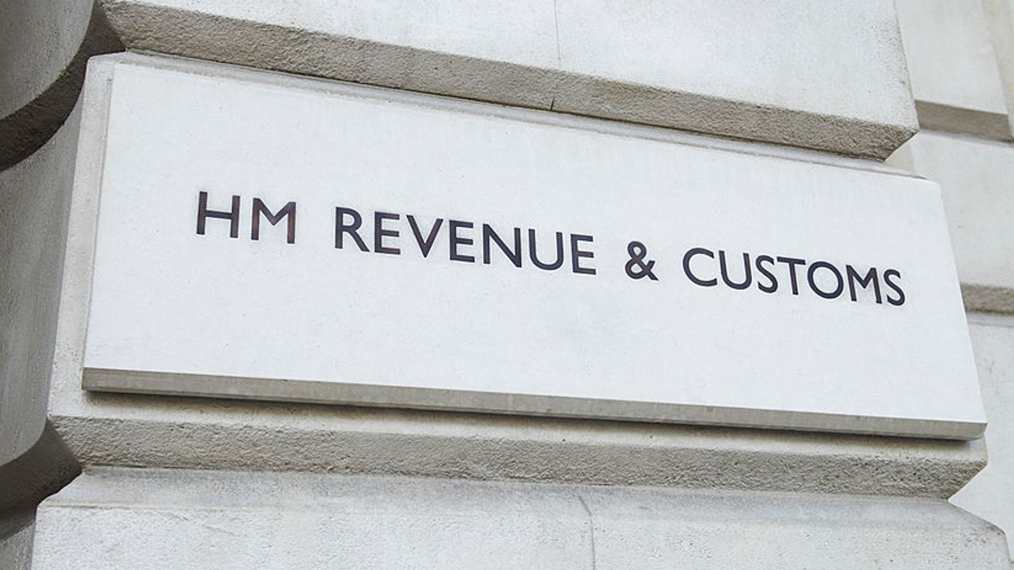 sign reading HM REVENUE AND CUSTOMS on outside of building